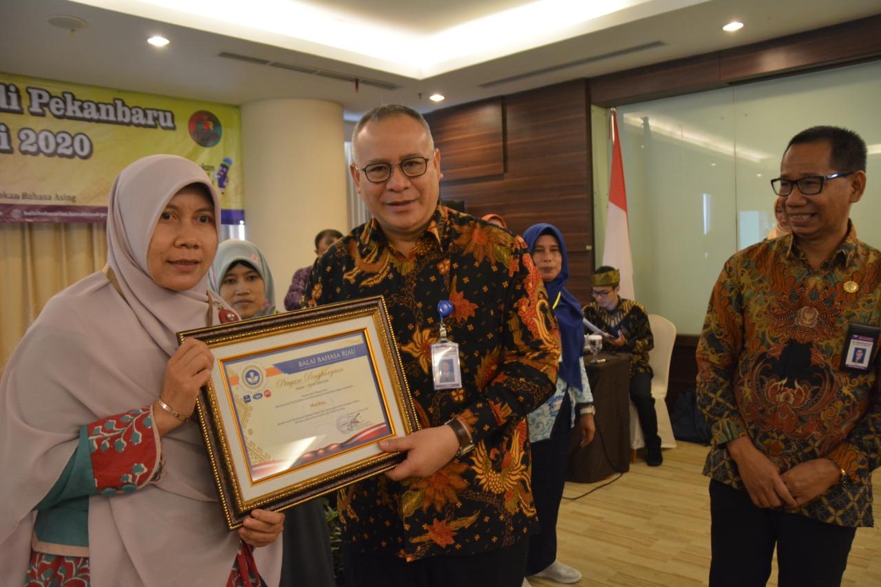 Marlina menerima penghargaan yang diserahkan oleh Kepala Badan Pengembangan Bahasa dan Perbukuan, Kemendikbud, Prof. Dr. Dadang Sunendar di Pekanbaru